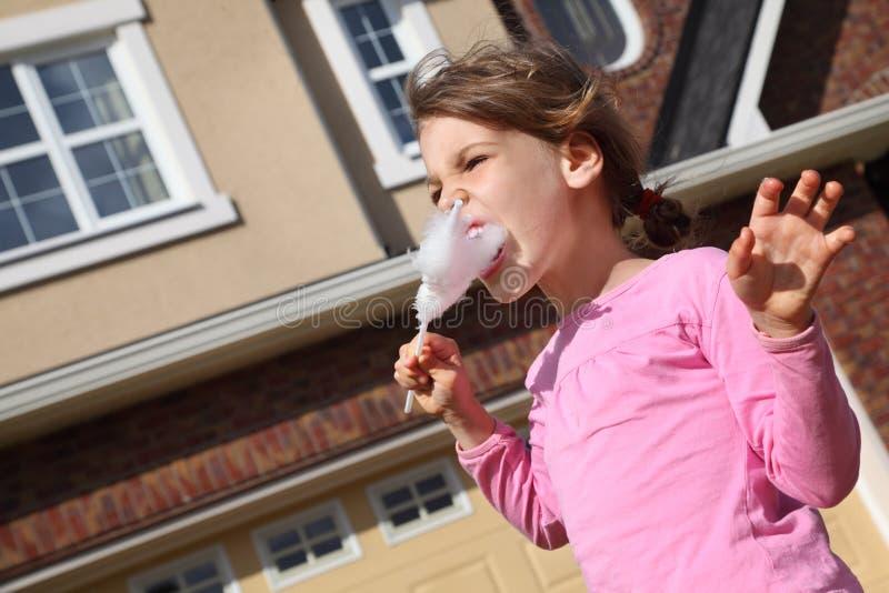 La bambina felice mangia la caramella di cotone immagine stock libera da diritti