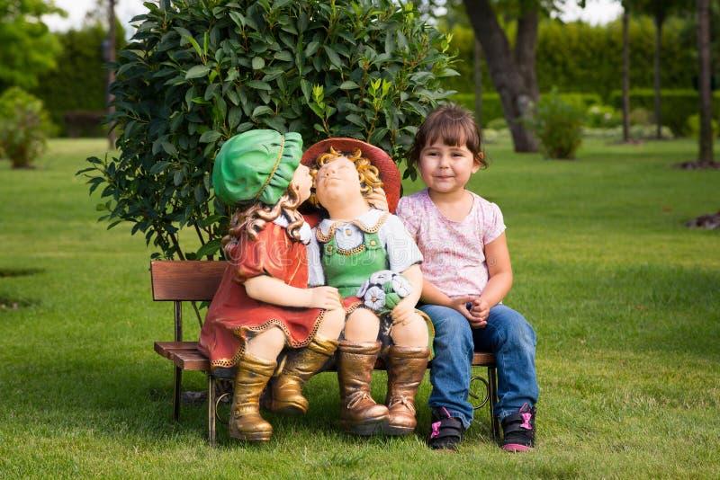 La bambina felice si diverte con le bambole del giardino immagini stock libere da diritti
