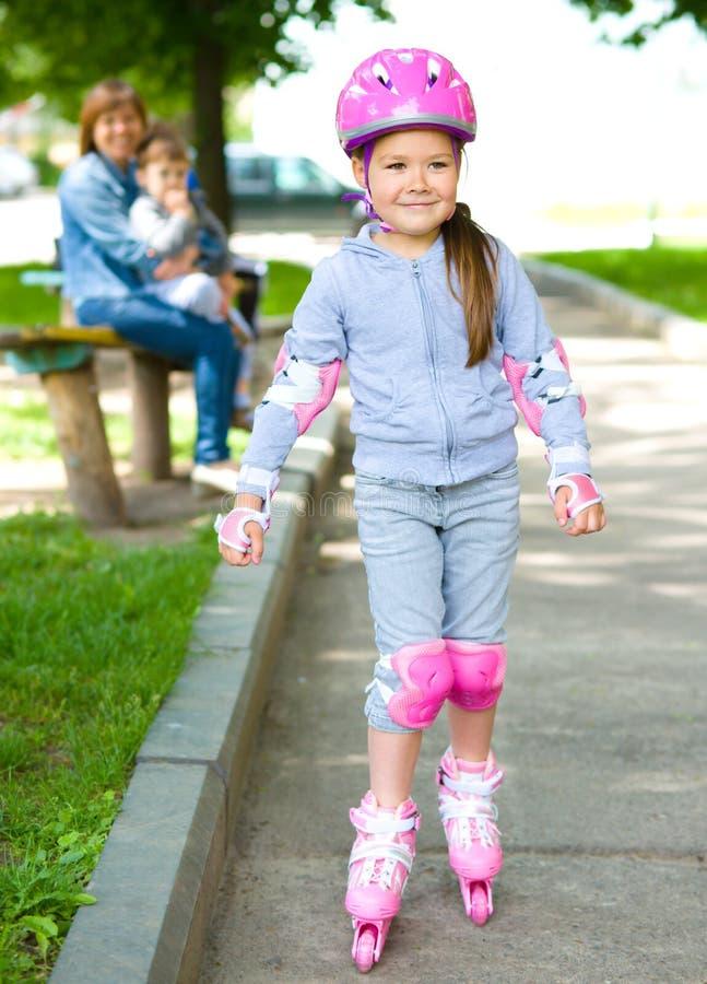 La bambina felice sta pattinando sui rulli fotografia stock libera da diritti