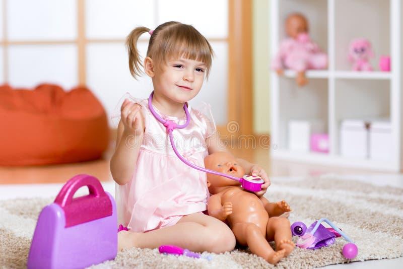 La bambina gioca al dottore esaminando un paziente della bambola fotografia stock libera da diritti