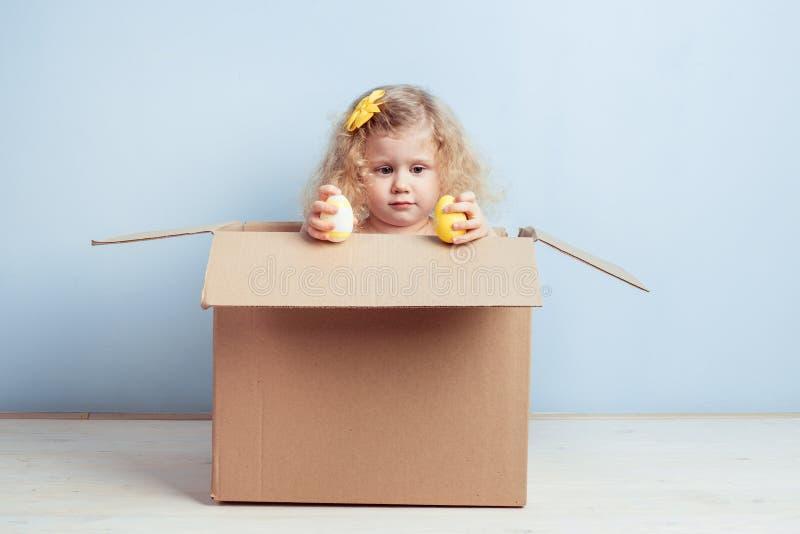 La bambina graziosa con il fiore giallo sui suoi capelli ed ha tinto le uova in sue mani si siede nella scatola di cartone sui pr fotografia stock libera da diritti