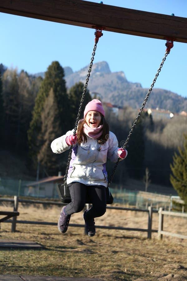 La bambina graziosa sta giocando su un campo da giuoco nelle montagne fotografia stock