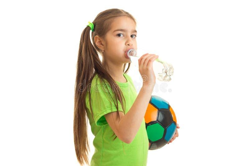 La bambina graziosa in uniforme di verde con pallone da calcio beve l'acqua fotografia stock libera da diritti