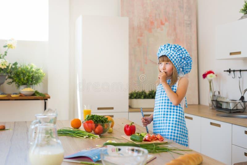 La bambina graziosa in vestiti del cuoco ha trovato un'idea su una cucina fotografia stock libera da diritti