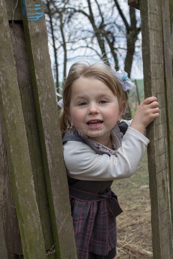 La bambina guarda con il portone di legno fotografia stock libera da diritti