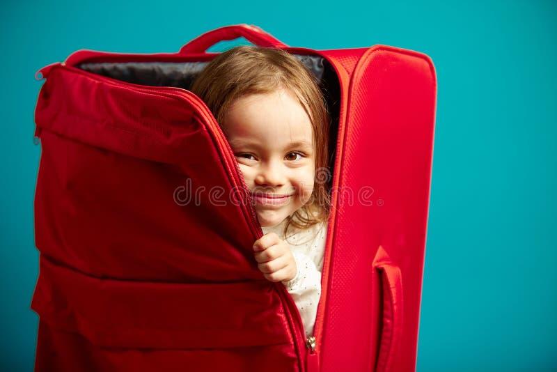 La bambina guarda dalla valigia rossa su fondo isolato blu immagine stock