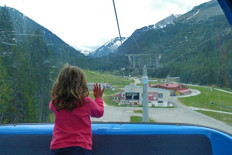 La bambina guarda fuori la finestra dell'ascensore di sci fotografia stock