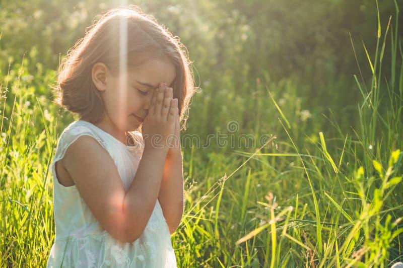 La bambina ha chiuso i suoi occhi, pregare in un campo durante il bello tramonto Mani piegate nel concetto di preghiera per fede fotografia stock
