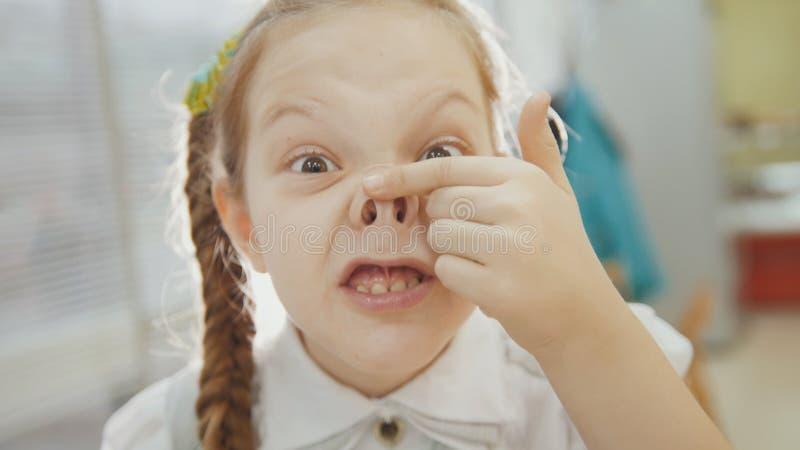 La bambina ha divertente, sorridendo e mostra il naso di porcellino fotografie stock