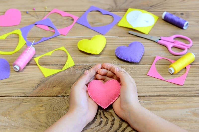 La bambina ha fatto gli ornamenti di un cuore del feltro Ragazza che tiene un cuore del feltro in sue mani Mestieri per il giorno fotografia stock libera da diritti