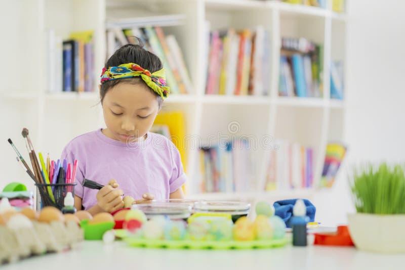 La bambina impara dipingere le uova di Pasqua nella biblioteca immagini stock libere da diritti