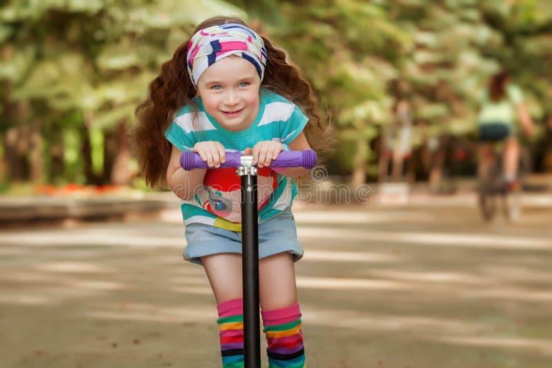 La bambina impara guidare il motorino in un parco il giorno di estate soleggiato fotografia stock
