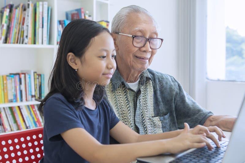 La bambina impara utilizzare un computer portatile con suo nonno fotografie stock libere da diritti