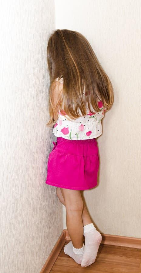 La bambina impertinente sta stando nell'angolo immagini stock