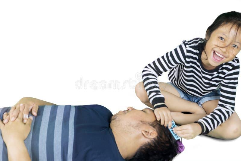La bambina indossa i bigodini a suo padre fotografie stock