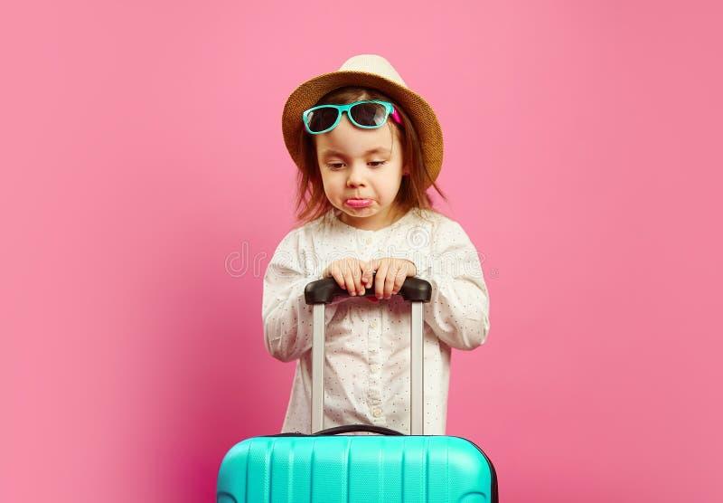 La bambina infastidita con i supporti della valigia sul cappello di paglia e sugli occhiali da sole isolati e d'usi rosa, esprime fotografia stock