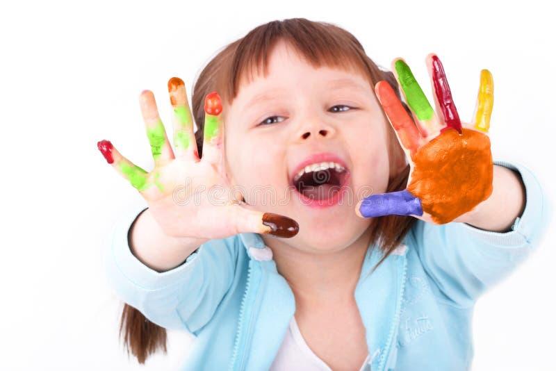 La bambina la mostra che ha colorato le mani immagini stock