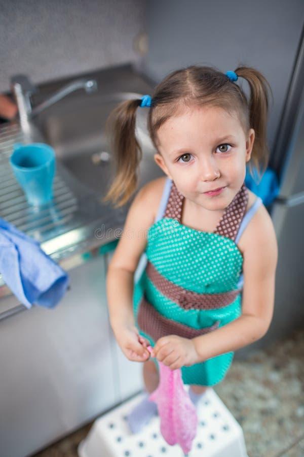 La bambina lava i piatti a casa nella cucina immagini stock