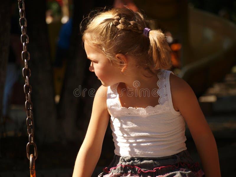 La bambina in maglietta bianca sta sedendosi su un'oscillazione immagini stock