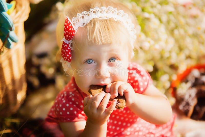 La bambina mangia i biscotti del cioccolato fotografia stock libera da diritti