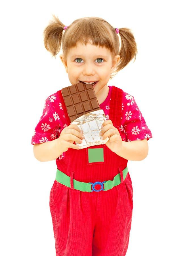 La bambina mangia il cioccolato immagini stock libere da diritti