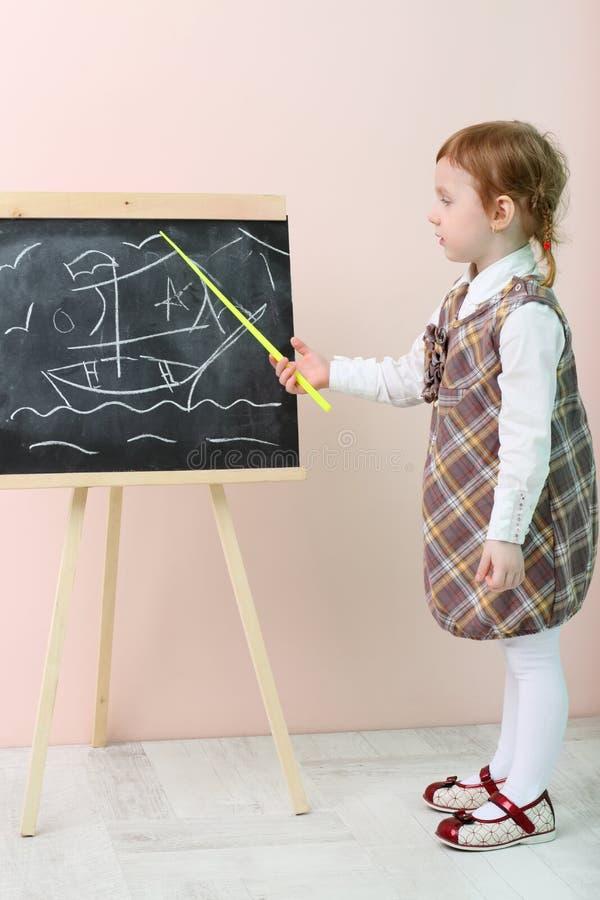 La bambina mostra in nave gialla del puntatore alla lavagna fotografia stock