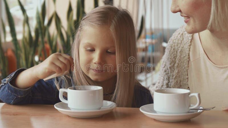 La bambina muove il cucchiaio nella tazza immagini stock