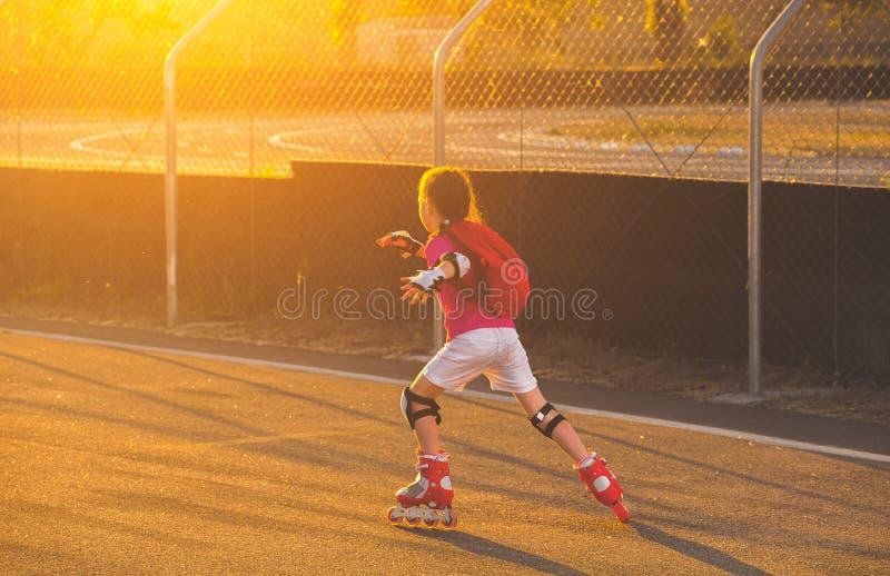la bambina negli shorts bianchi ed in una maglietta rosa sta pattinando sul ruolo di kah al tramonto fotografia stock