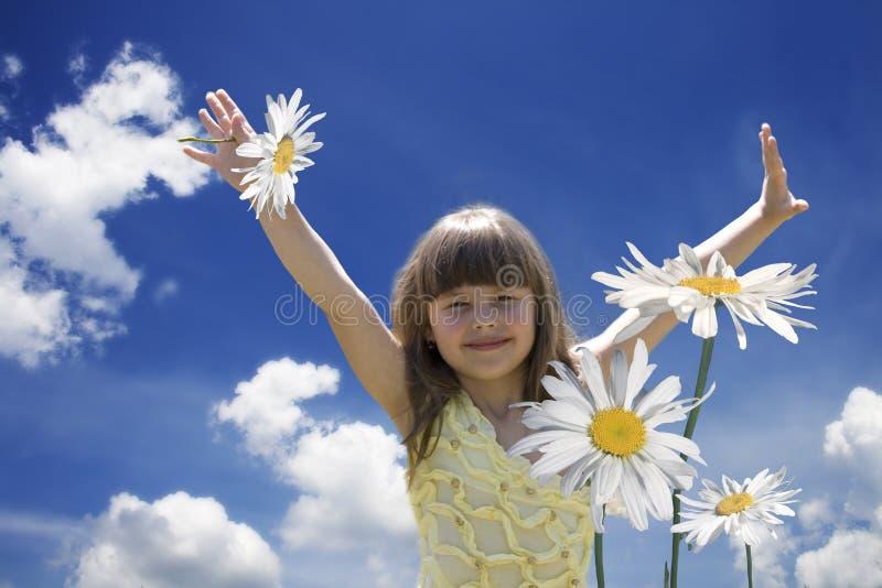 La bambina nei camomiles fotografia stock