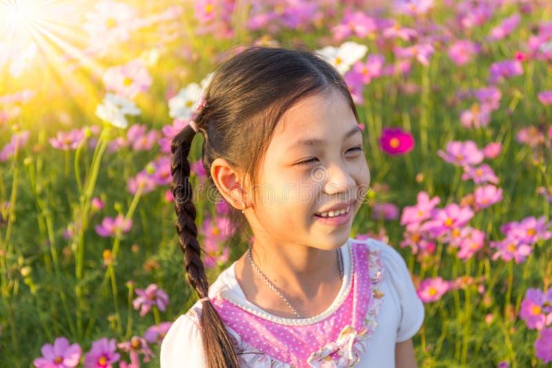 La bambina nel campo dell'universo rosa Bipin del fiore dell'universo fotografia stock libera da diritti