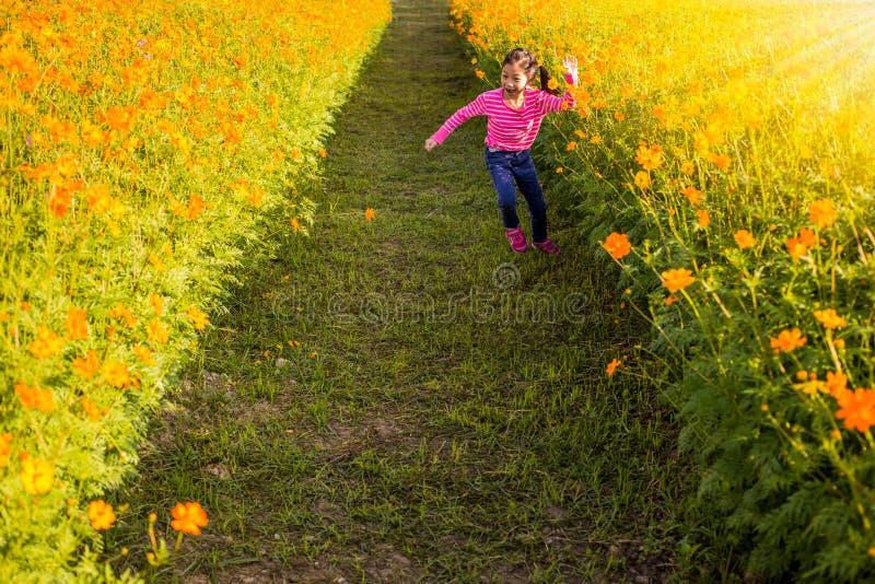 La bambina nel campo di giallo dell'universo fiorisce a sunligh immagine stock