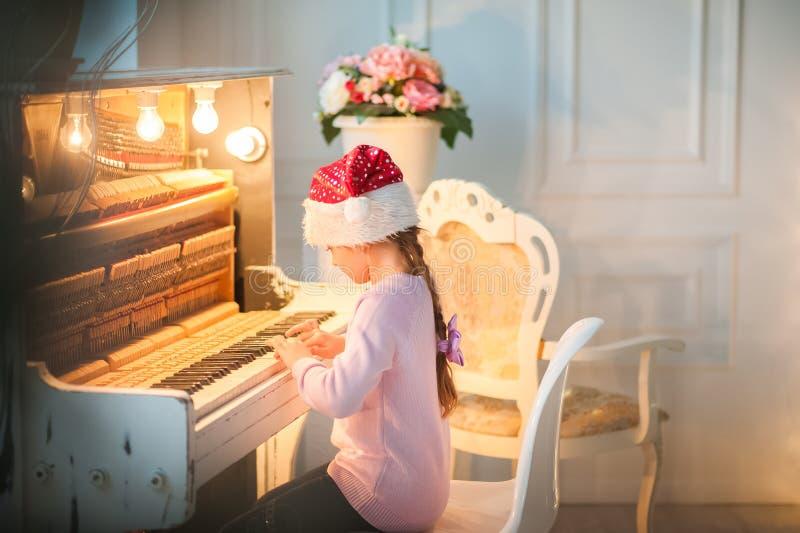 La bambina nel cappuccio di Santa Claus sta aspettando il nuovo anno La ragazza sul Natale sta giocando il piano fotografia stock libera da diritti