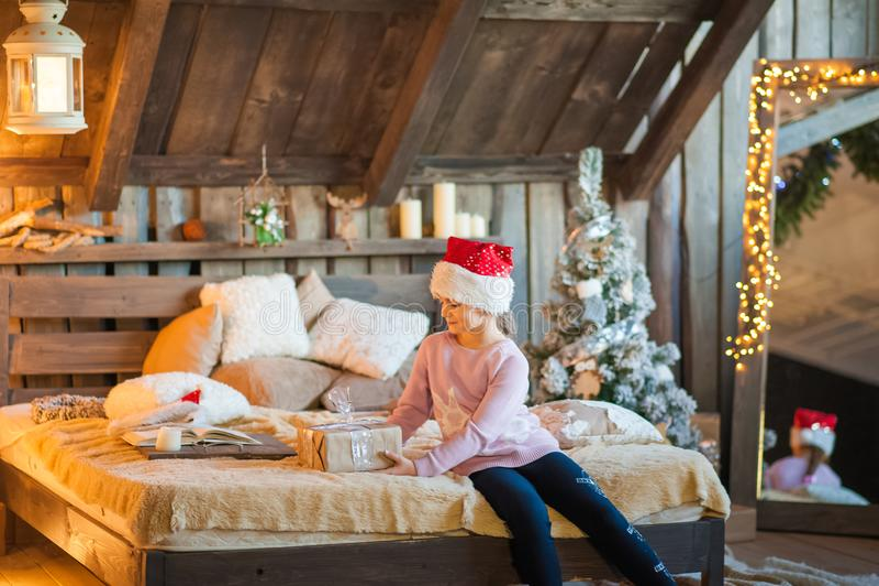 La bambina nel cappuccio di Santa Claus sta aspettando il nuovo anno sul letto Ragazza sul Natale con i regali nella camera da le fotografia stock libera da diritti