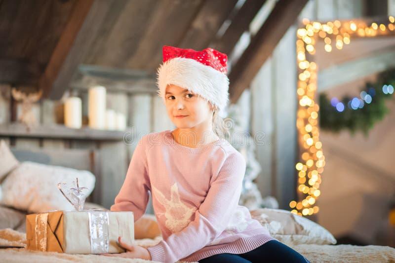 La bambina nel cappuccio di Santa Claus sta aspettando il nuovo anno sul letto Ragazza sul Natale con i regali nella camera da le fotografie stock libere da diritti