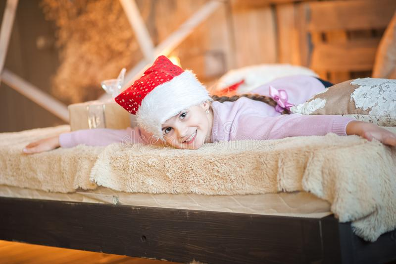 La bambina nel cappuccio di Santa Claus sta aspettando il nuovo anno sul letto Ragazza sul Natale con i regali nella camera da le fotografie stock