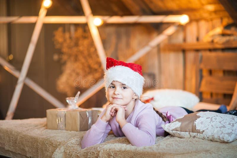 La bambina nel cappuccio di Santa Claus sta aspettando il nuovo anno sul letto Ragazza sul Natale con i regali nella camera da le fotografia stock