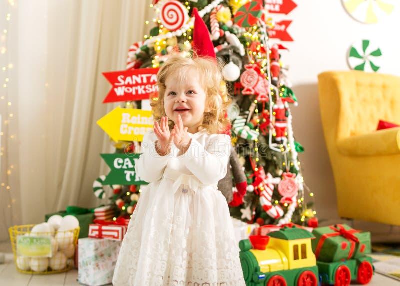 La bambina nel natale sta sotto un albero di Natale nel bianco immagini stock