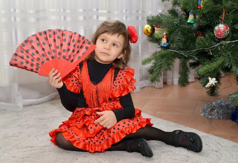 La bambina nel vestito spagnolo con un fan si siede circa un treeNew del nuovo anno fotografia stock libera da diritti