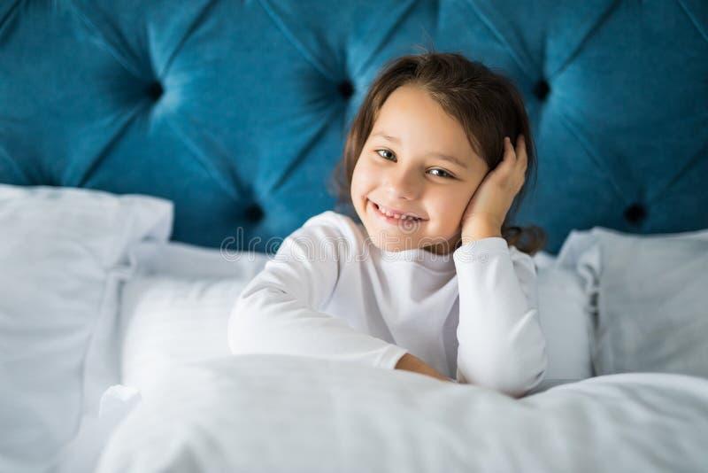 La bambina nella camera da letto sta sedendosi sul letto La bambina è durare pigiami Ragazza che si siede a letto fotografia stock libera da diritti