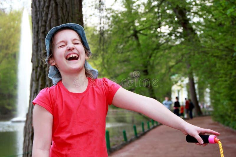 La bambina nelle risate del Panama gaio, chiudendo i suoi occhi con piacere, sulla via immagine stock libera da diritti