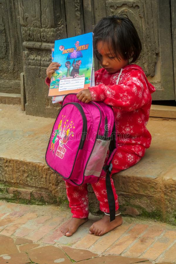 La bambina nepalese con i libri e la piccola scuola backpack fotografia stock libera da diritti