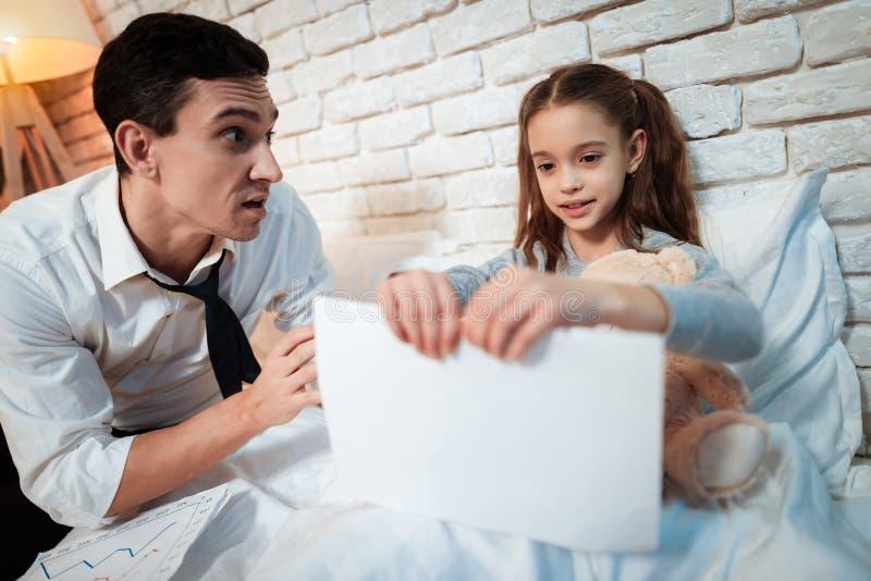 La bambina non lascia suo padre lavorare La piccola figlia sta strappando sulle sue carte del ` s del padre immagini stock libere da diritti