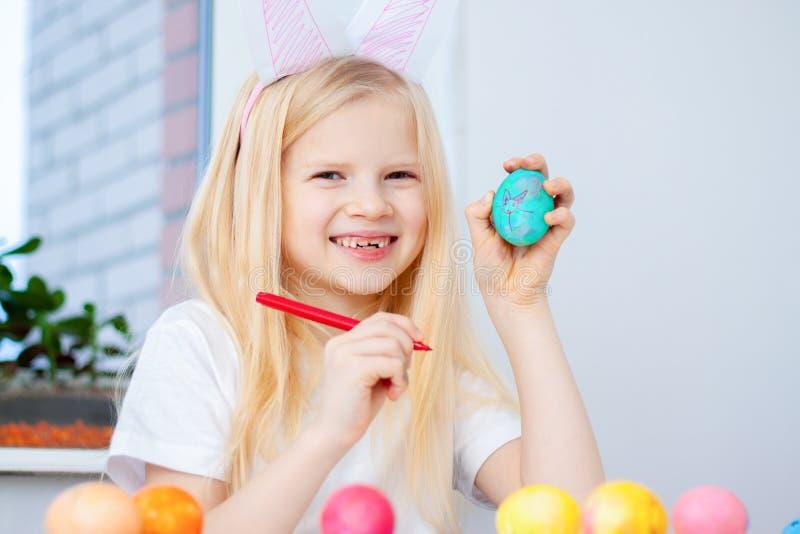 La bambina in orecchie del coniglietto del coniglio sulla testa sta preparando per Pasqua e le uova di verniciatura Indicatori va immagini stock libere da diritti