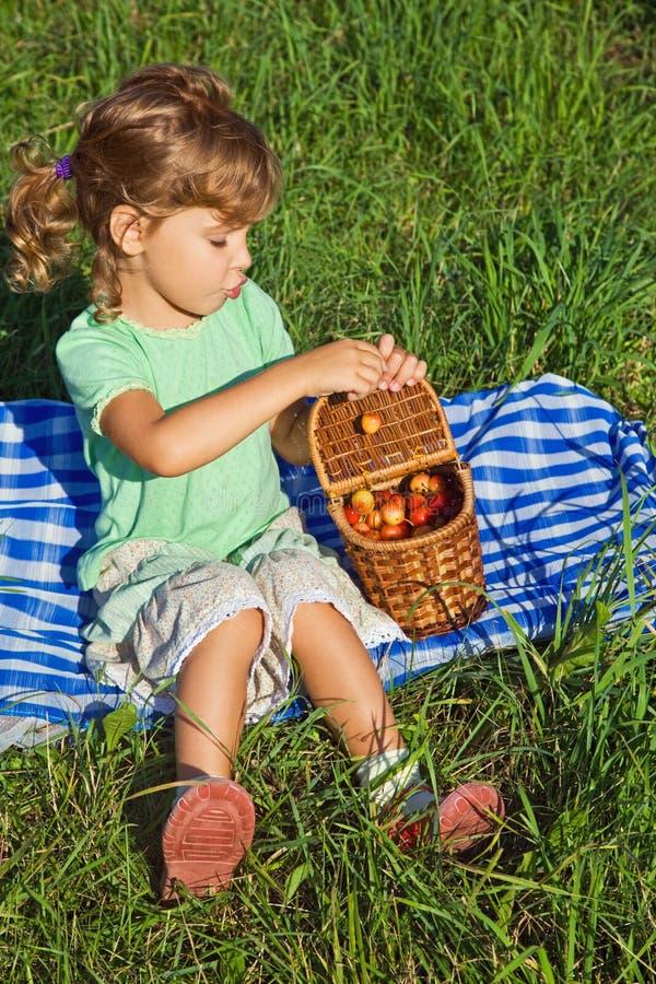 La bambina otterrà dalle ciliegie del cestino fotografia stock