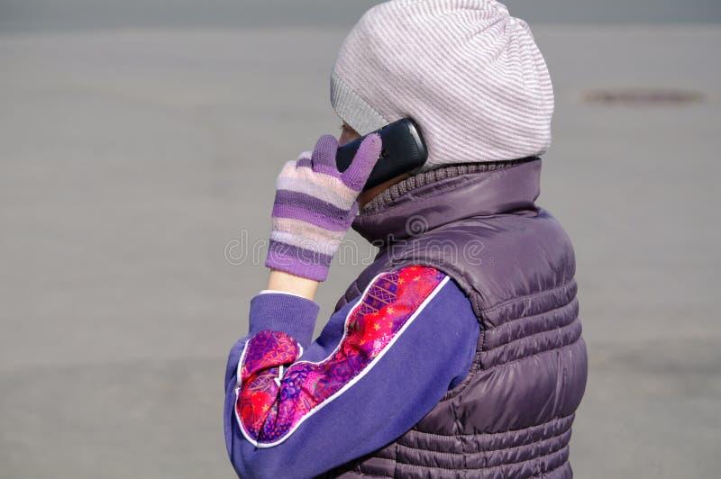 La bambina parla dal telefono cellulare mentre sta all'aperto immagine stock libera da diritti