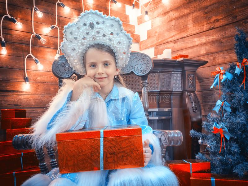 La bambina piacevole ha peso i gomiti su una scatola con i regali ed i sorrisi immagini stock libere da diritti
