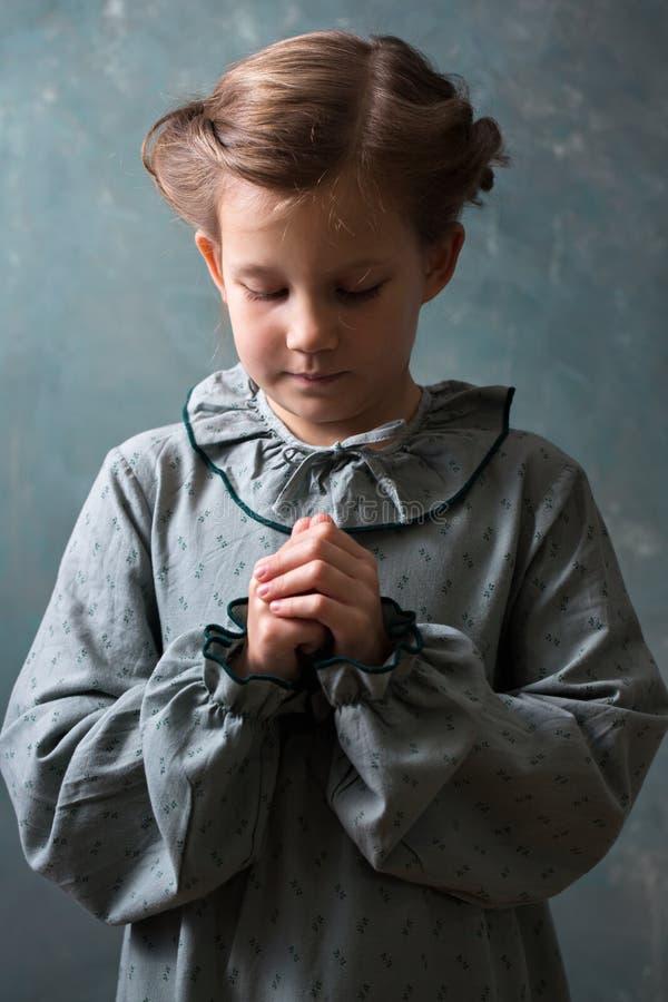 La bambina prega a Dio immagini stock libere da diritti
