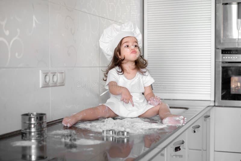 La bambina produce la pasta sulla cucina con il matterello fotografia stock libera da diritti