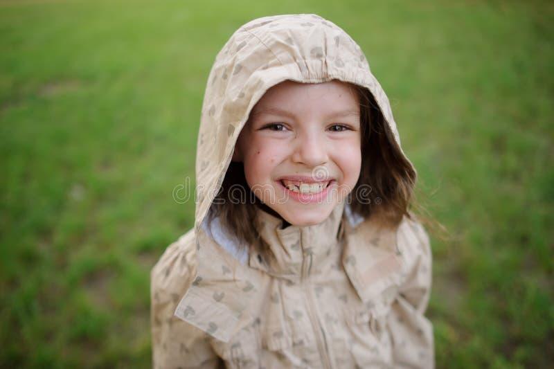 La bambina ridicola guarda in una macchina fotografica e sorride fotografia stock libera da diritti