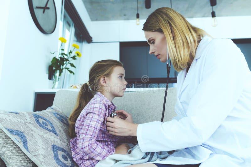 La bambina si è ammalata Un medico è venuto a lei ed ha ascoltato lei con uno stetoscopio immagine stock libera da diritti